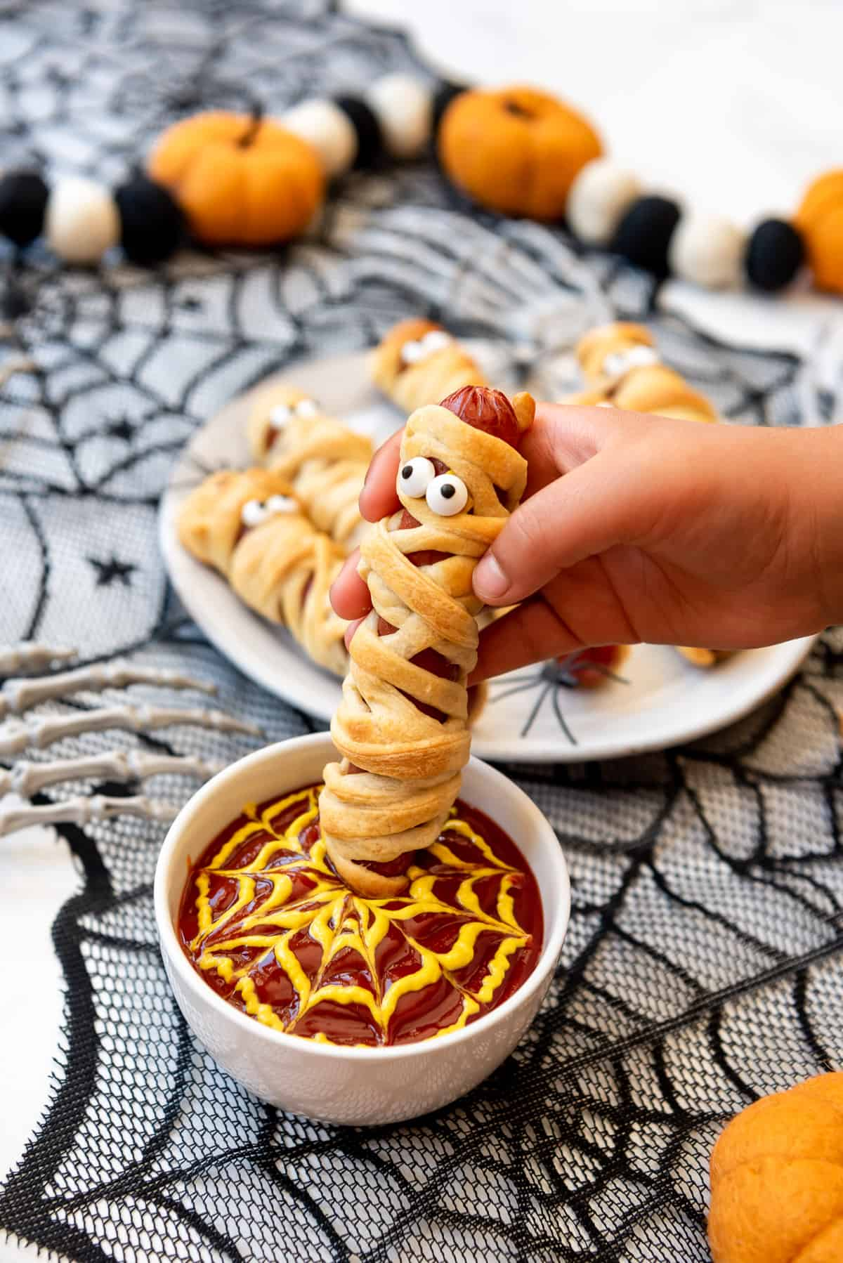 a child's hand dipping a Halloween mummy dog into a bowl of ketchup and mustard.