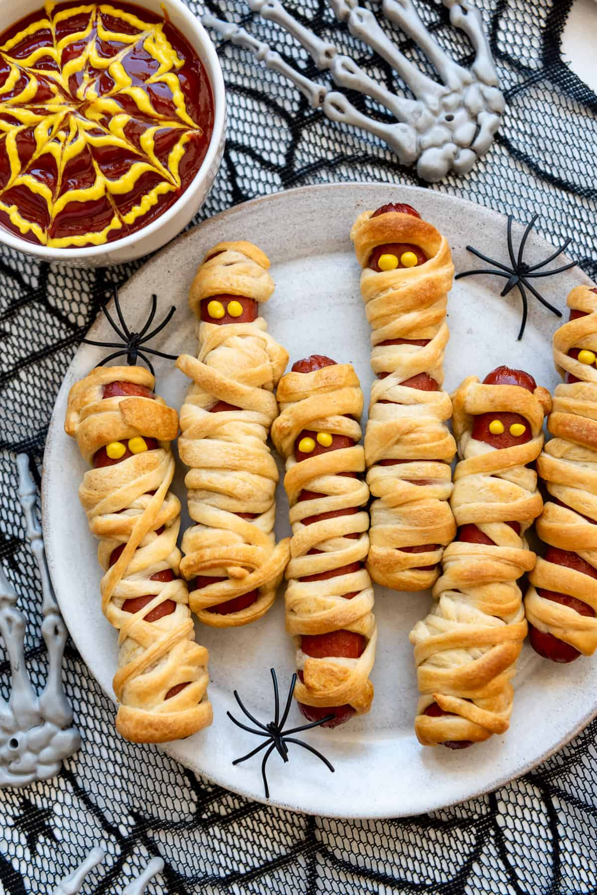 hot dogs wrapped in crescent roll dough with mustard eyes on a plate surrounded by plastic spiders.