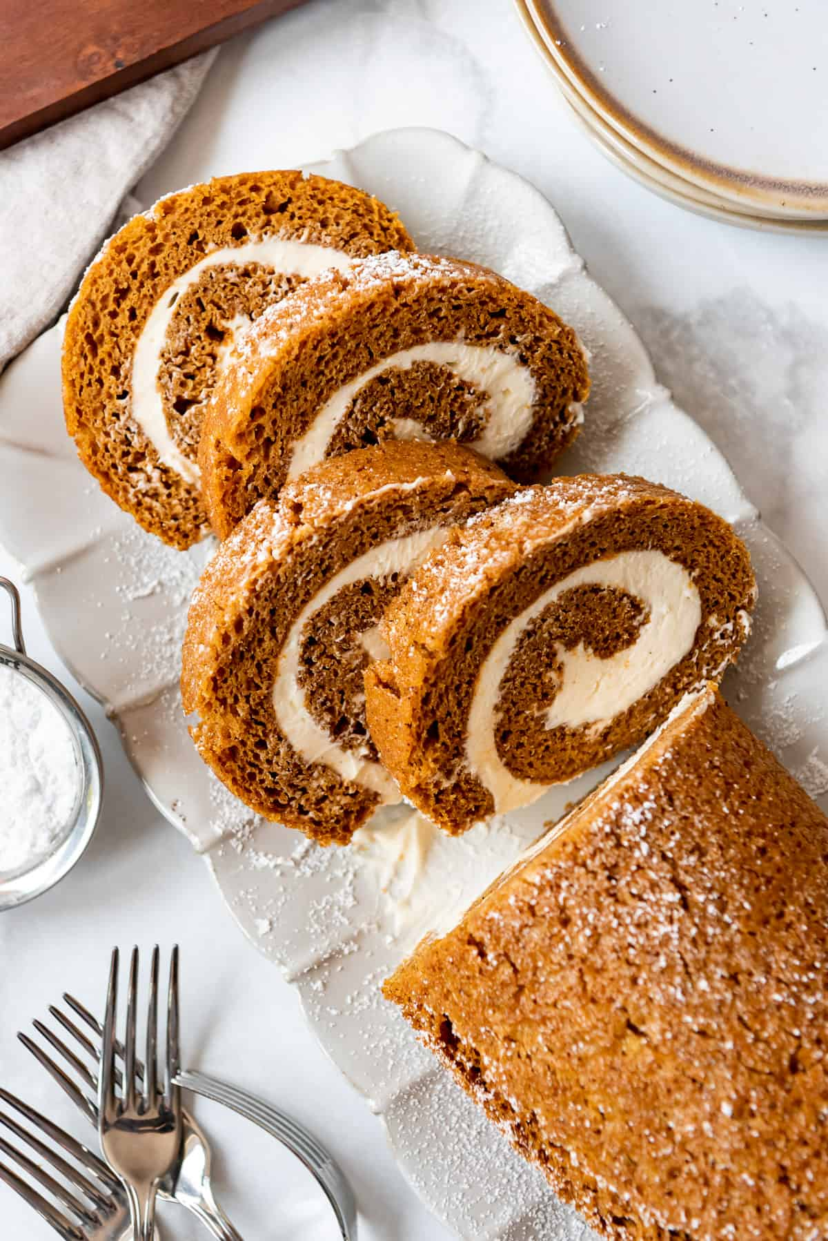 slices of pumpkin roll with cream cheese filling on a decorative plate.