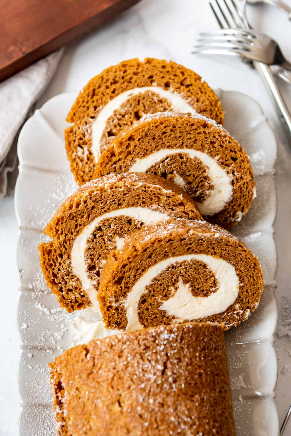 four slices of pumpkin swiss cake roll on a white plate.