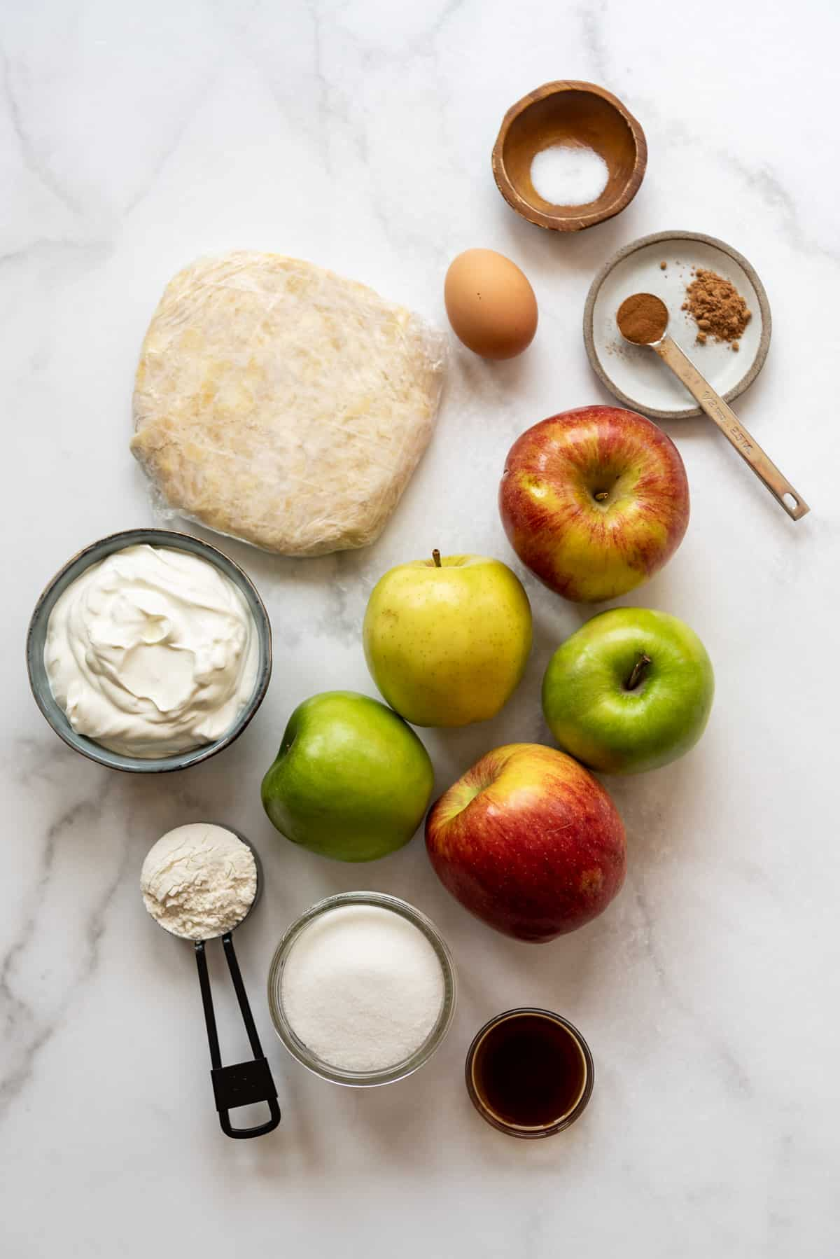 Sour cream apple pie filling ingredients on a white surface.