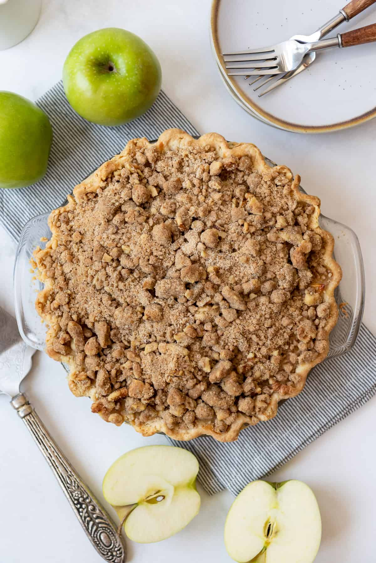 An apple pie topped with a brown sugar walnut streusel topping on a striped napkin.