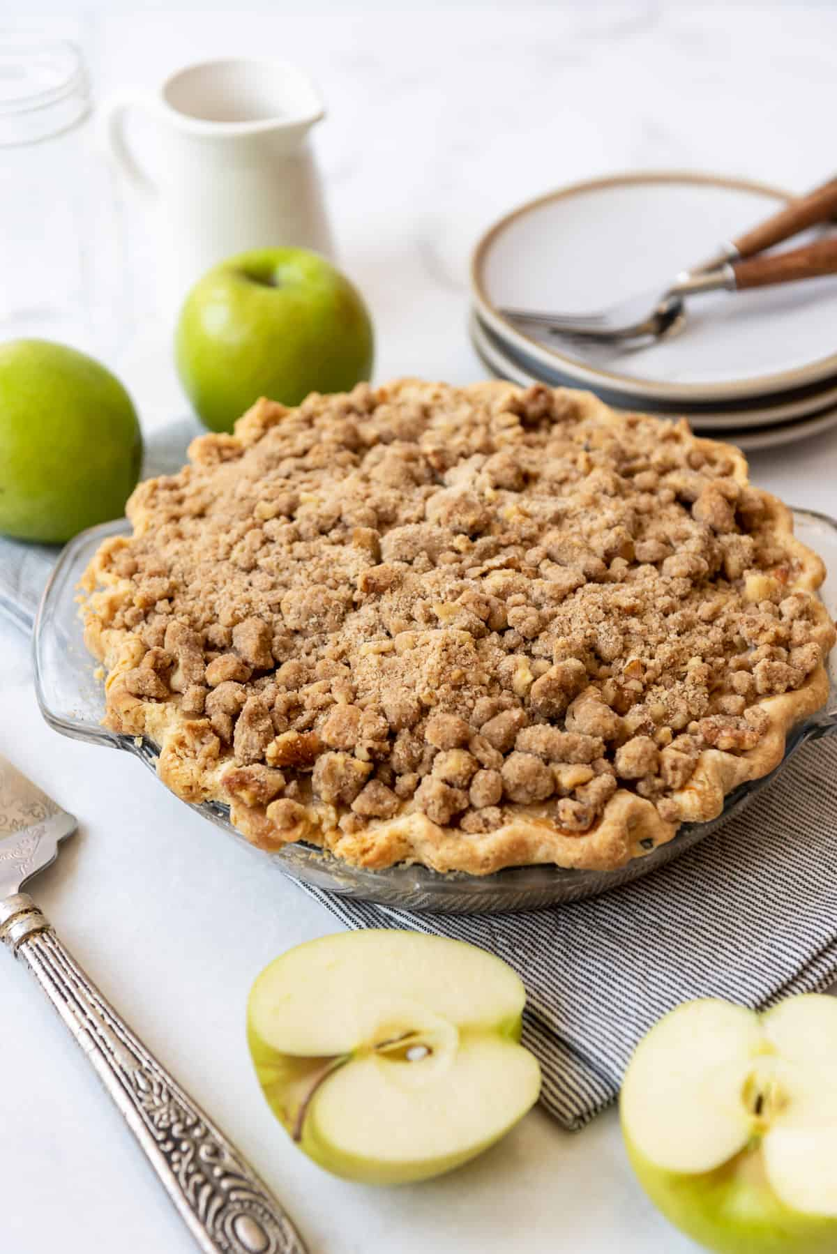 A sour cream apple pie topped with streusel next to Granny Smith apples.