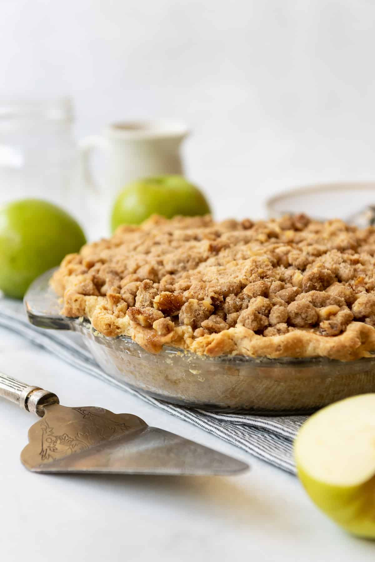 A baked sour cream apple pie in a glass pie plate.