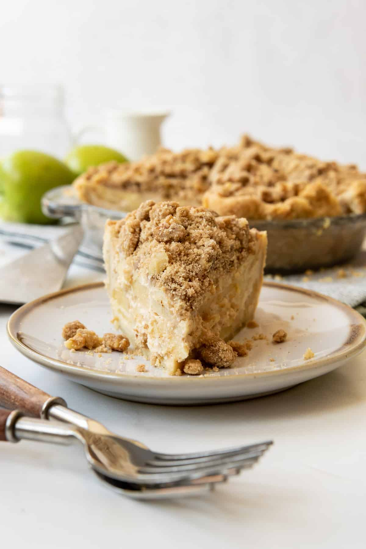A slice of sour cream apple pie on a plate.