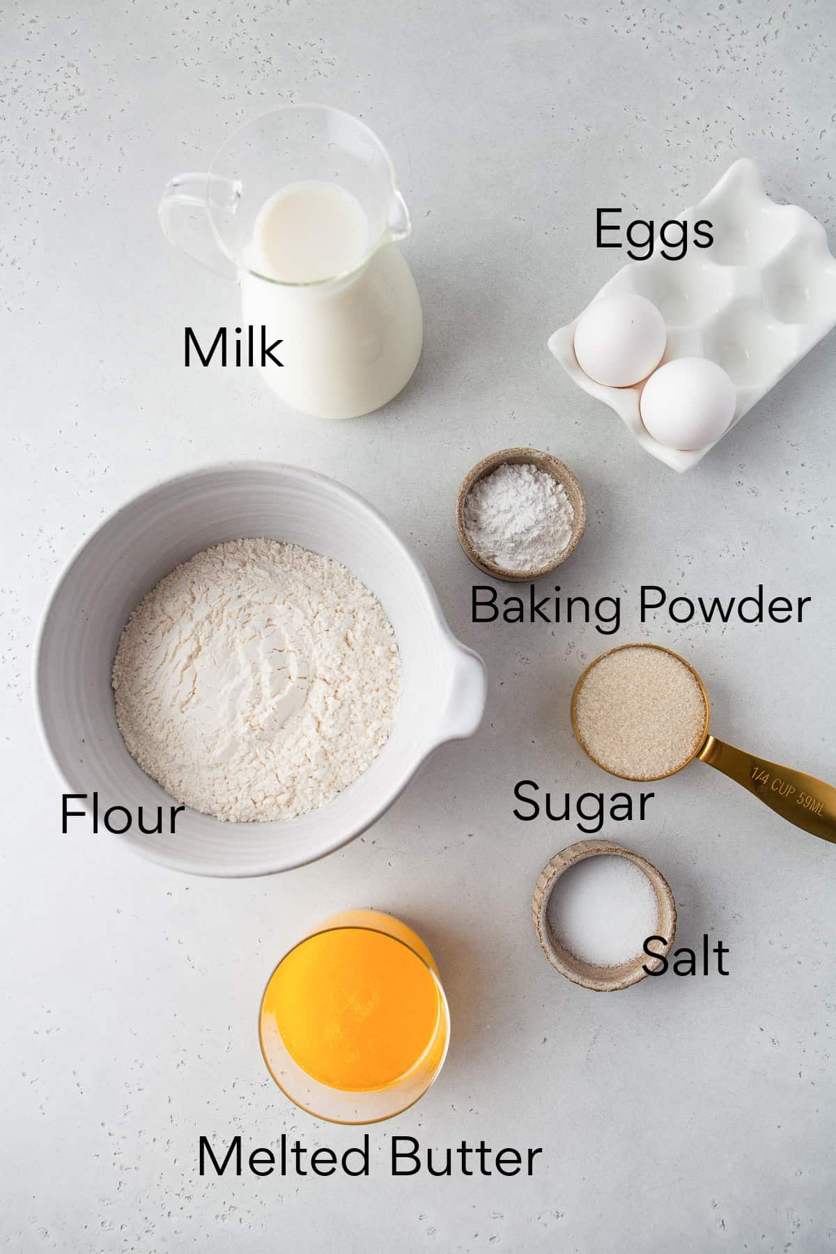 milk, eggs, baking powder, flour, sugar, salt, and butter in separate containers