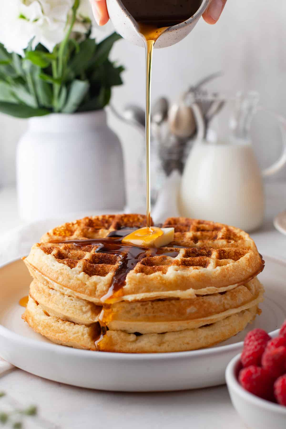 a stack of three waffles on a plate with syrup being drizzled over a pat of butter on top.