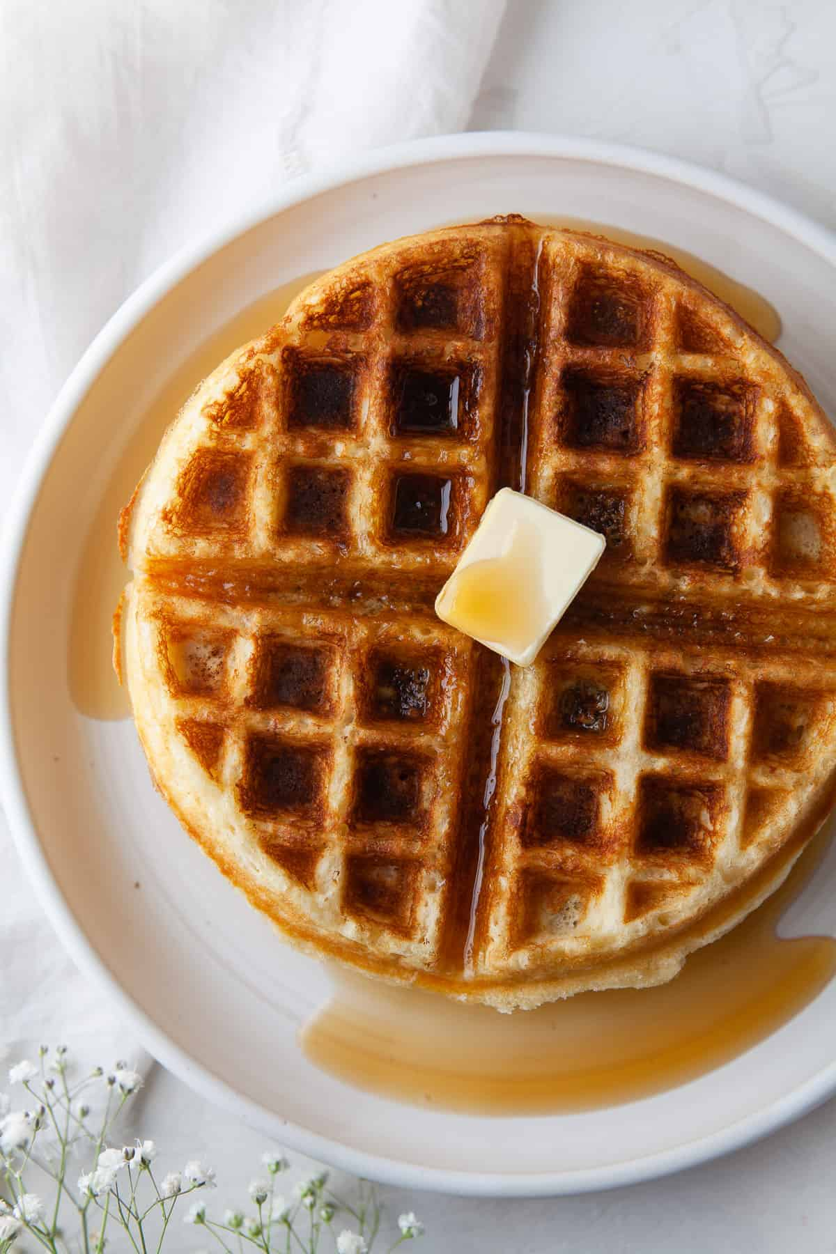 a round belgian waffle topped with a pat of butter and maple syrup on a plate