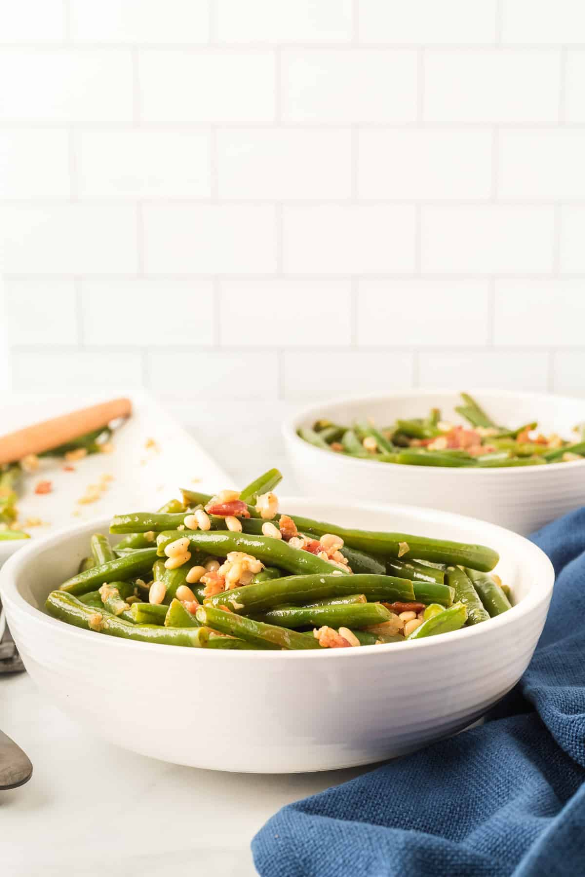 a white bowl next to a blue napkin filled with green beans, bacon, and pine nuts.