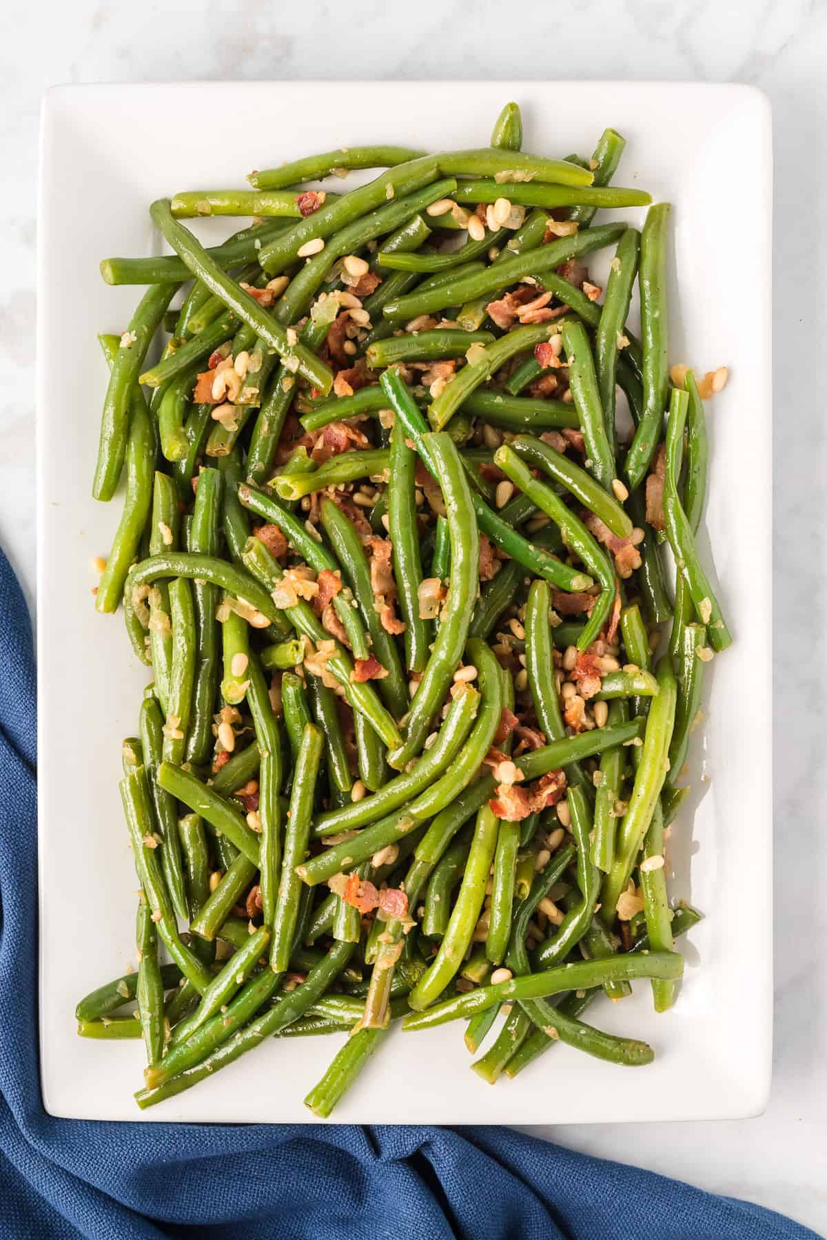 a large white serving plate with fresh green beans with bacon and pine nuts.