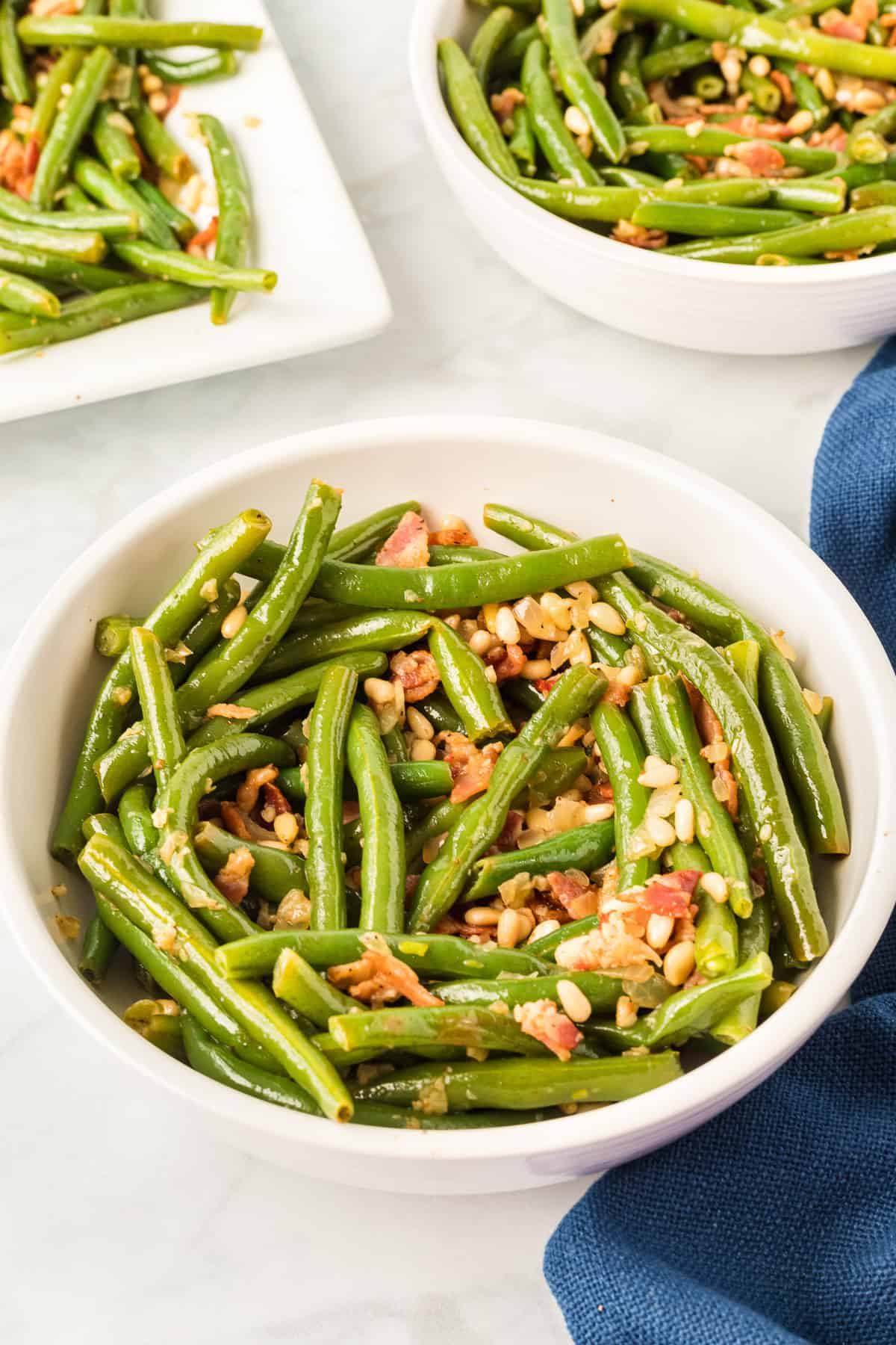 a white bowl with a serving of green beans with bacon and pine nuts.