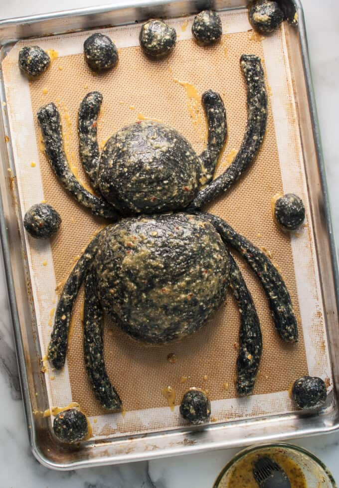 A Halloween appetizer bread bowl shaped like a spider brushed with garlic herb egg wash.