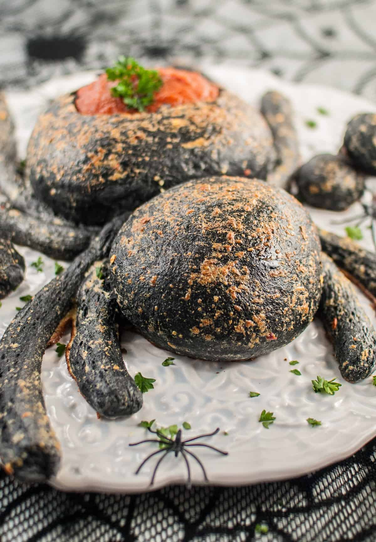 A Halloween spider bread bowl appetizer on a white plate.