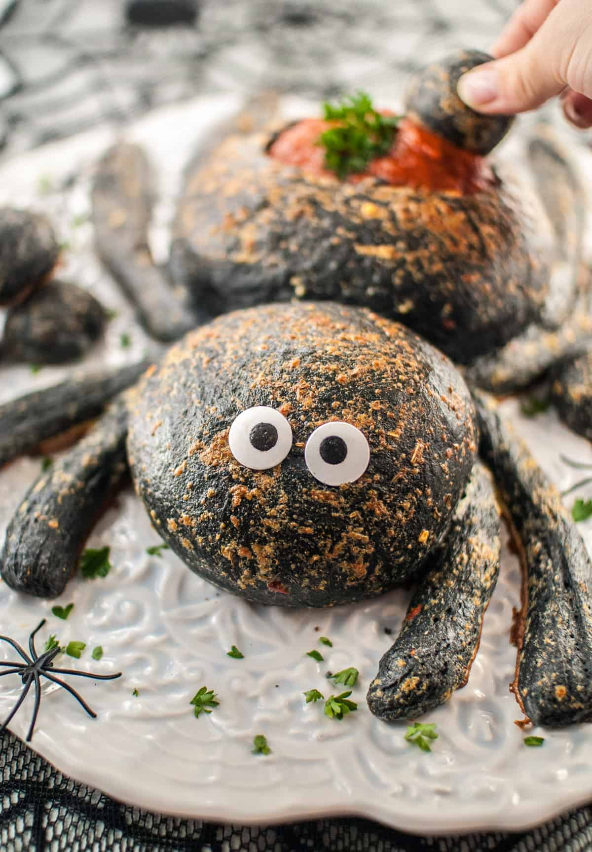 A cute Halloween spider bread bowl appetizer on a white plate.