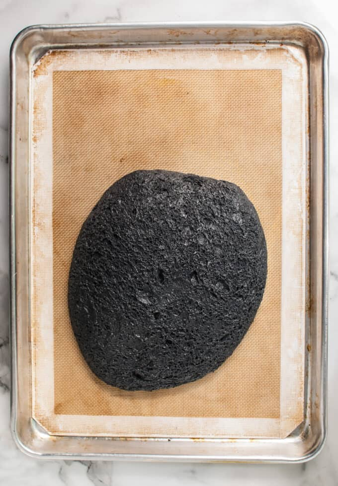 Black bread dough made with activated charcoal powder turned out onto a baking mat.