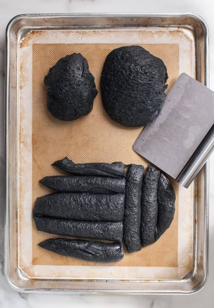 Black bread dough divided into pieces for shaping into a spider.