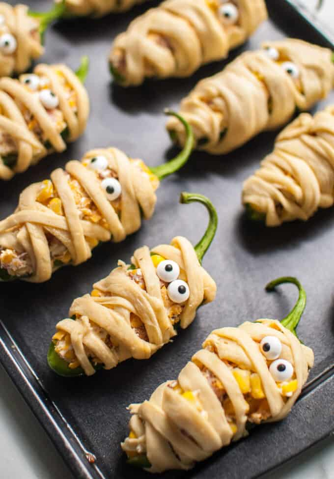 Mummy jalapeno poppers lined up on a baking sheet ready to be baked.