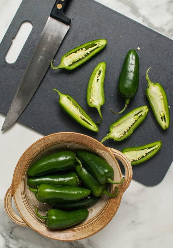 Fresh jalapenos sliced in half on a grey cutting board.