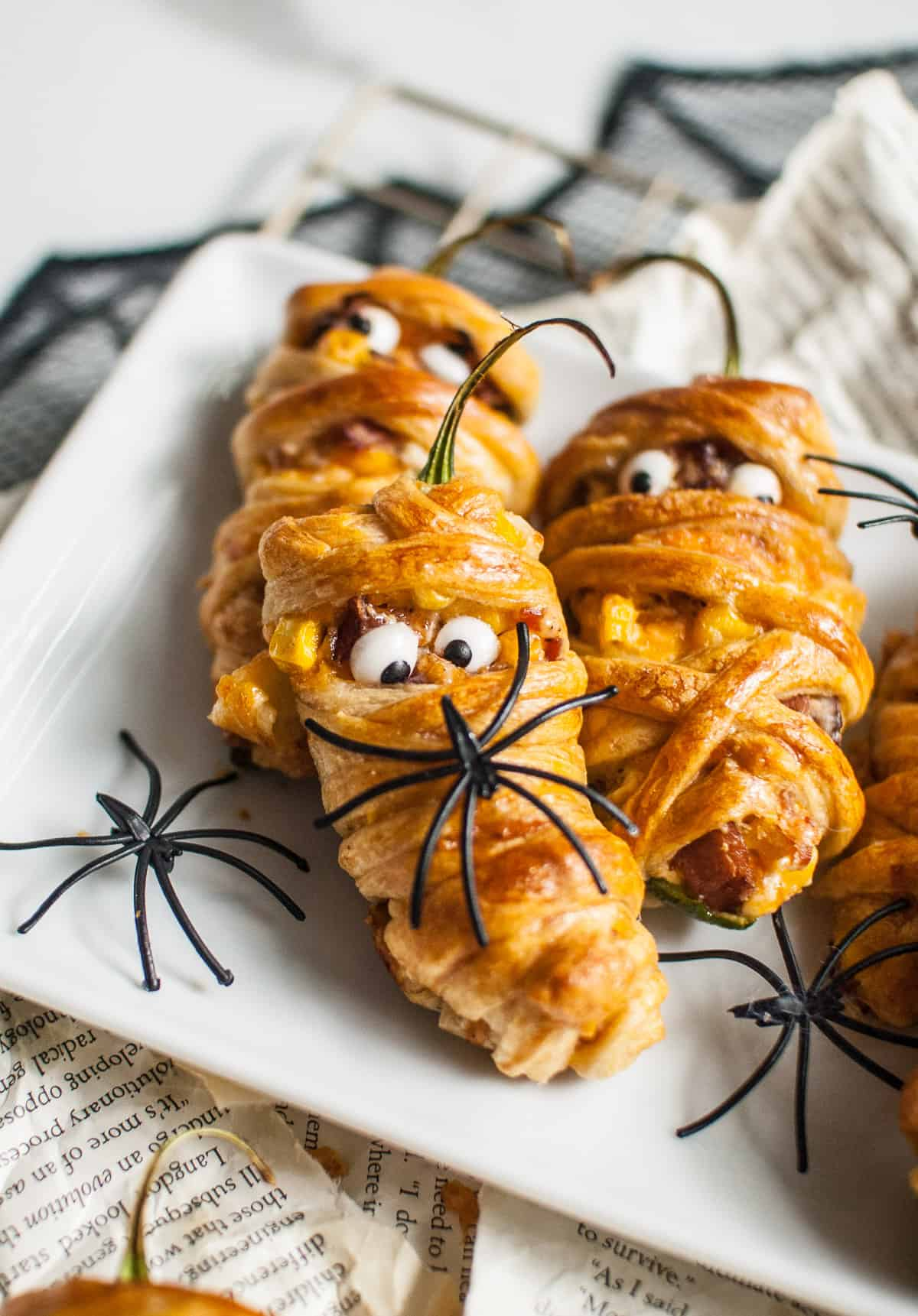 A jalapeno popper wrapped in crescent roll dough to look like a mummy with candy eyes looking cross-eyed at a plastic spider.