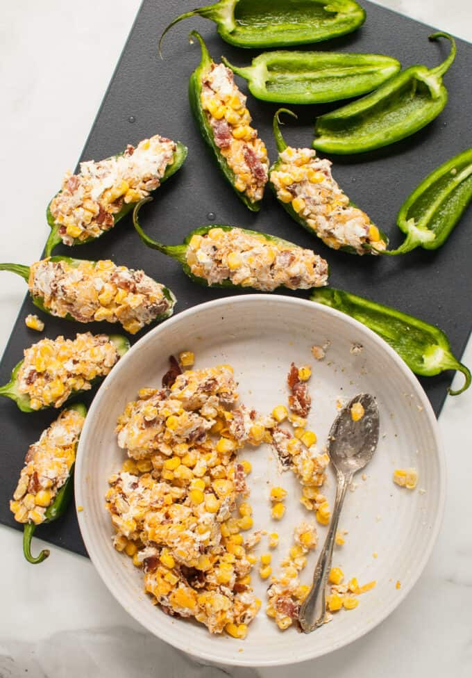 A bowl of corn and cream cheese filling next to jalapeno halves, some of which have been filled.