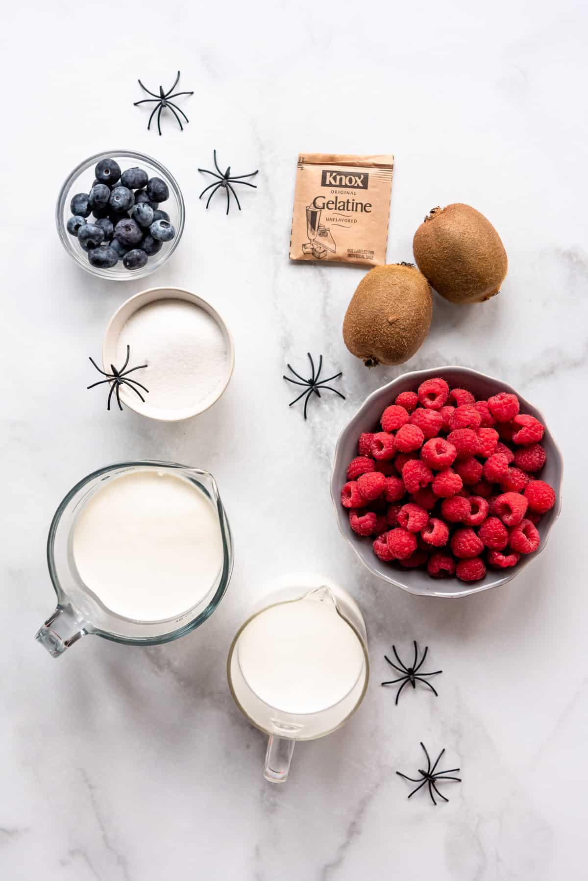 ingredients in separate bowls for making Halloween panna cotta with little plastic spiders surrounding them.