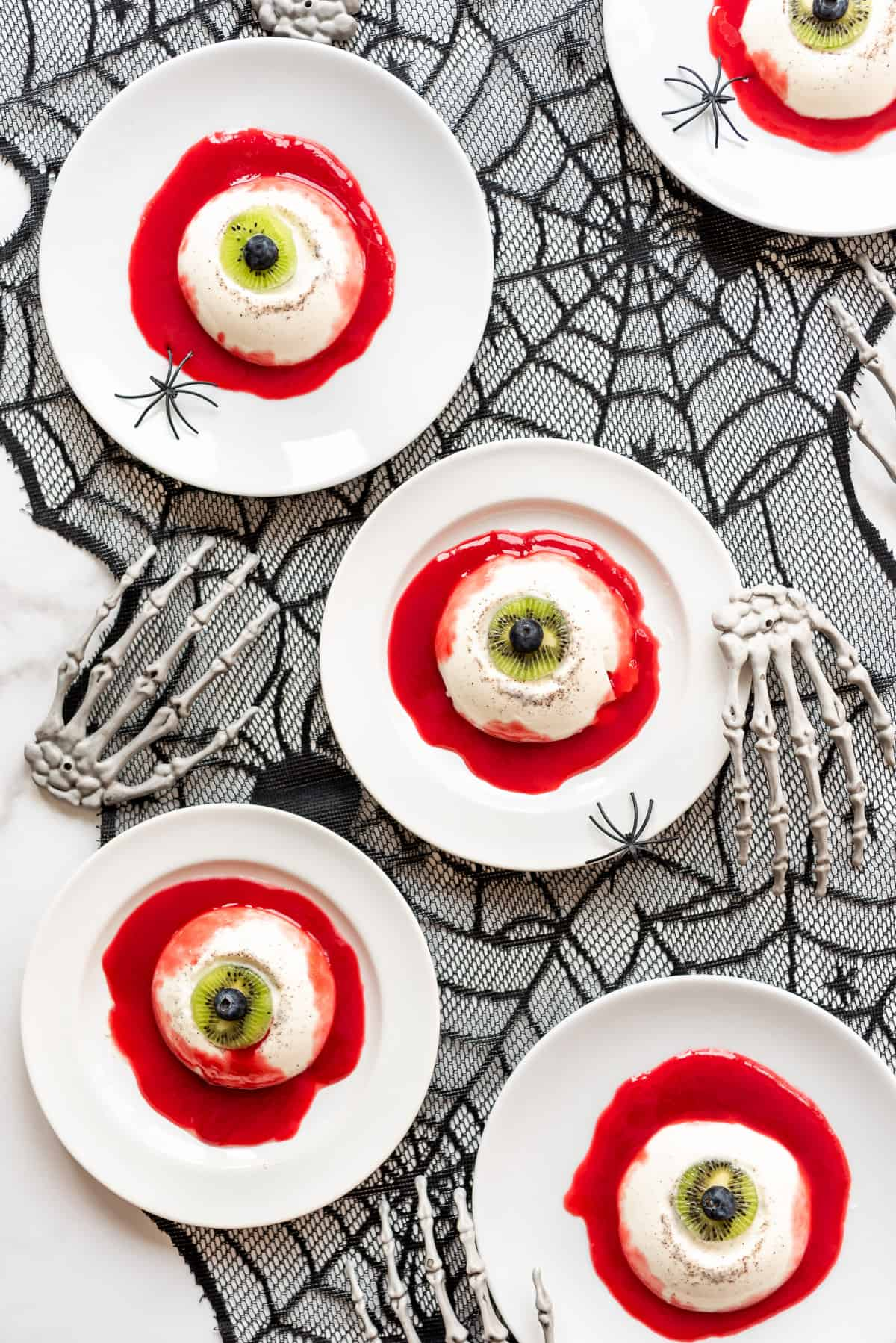 dessert plates on a spiderweb table runner with plastic skeleton hands and panna cotta eyeballs on them.