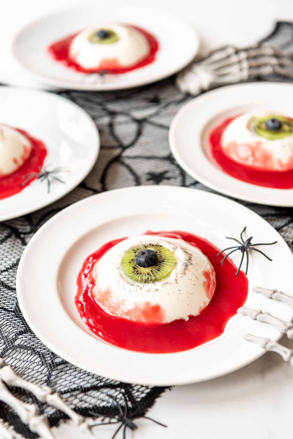 a spooky eyeball dessert made from panna cotta, kiwis, and raspberry coulis on white plates.