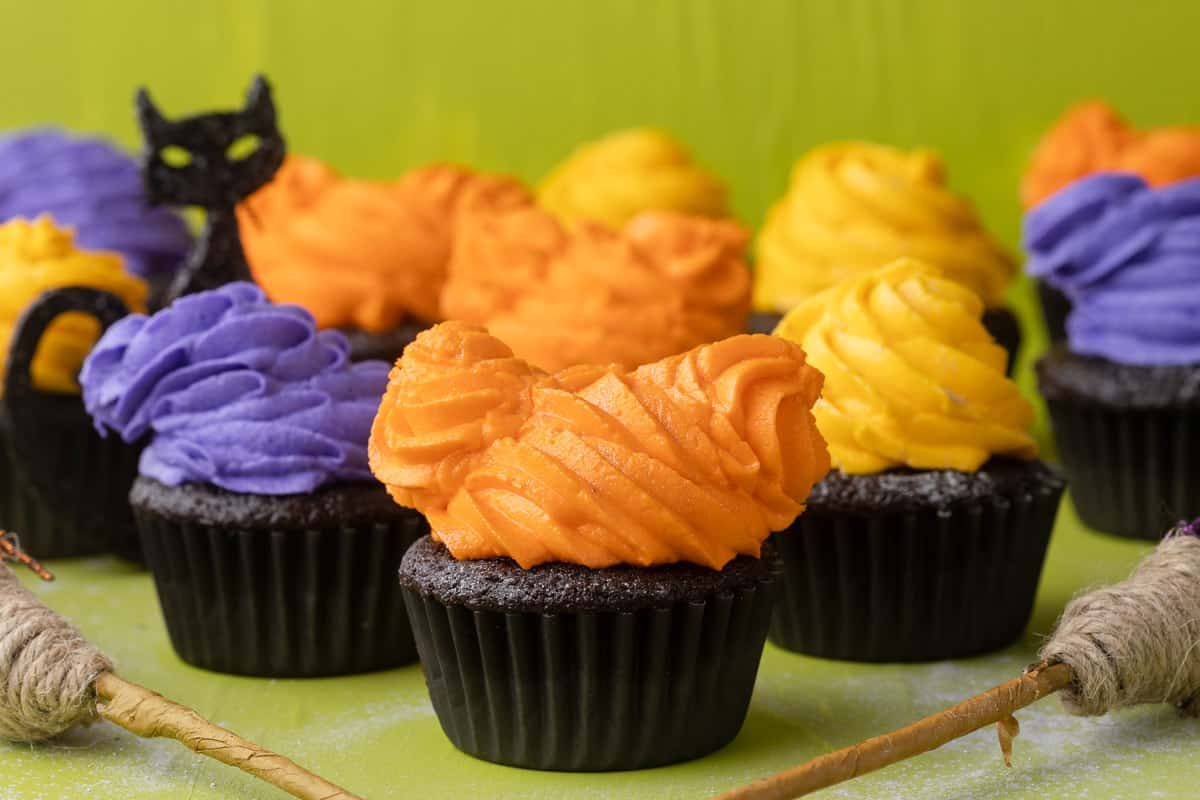 Chocolate cupcakes decorated with orange, purple, and yellow frosting swirls.