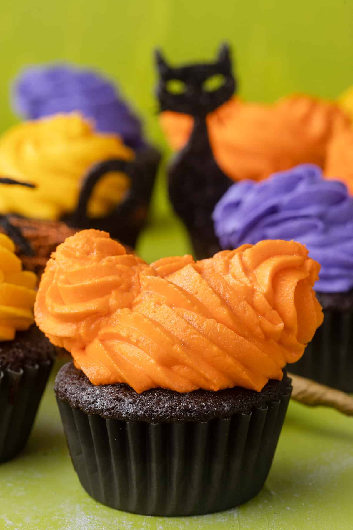 A chocolate cupcake with frosting piped to resemble the witches from Hocus Pocus.