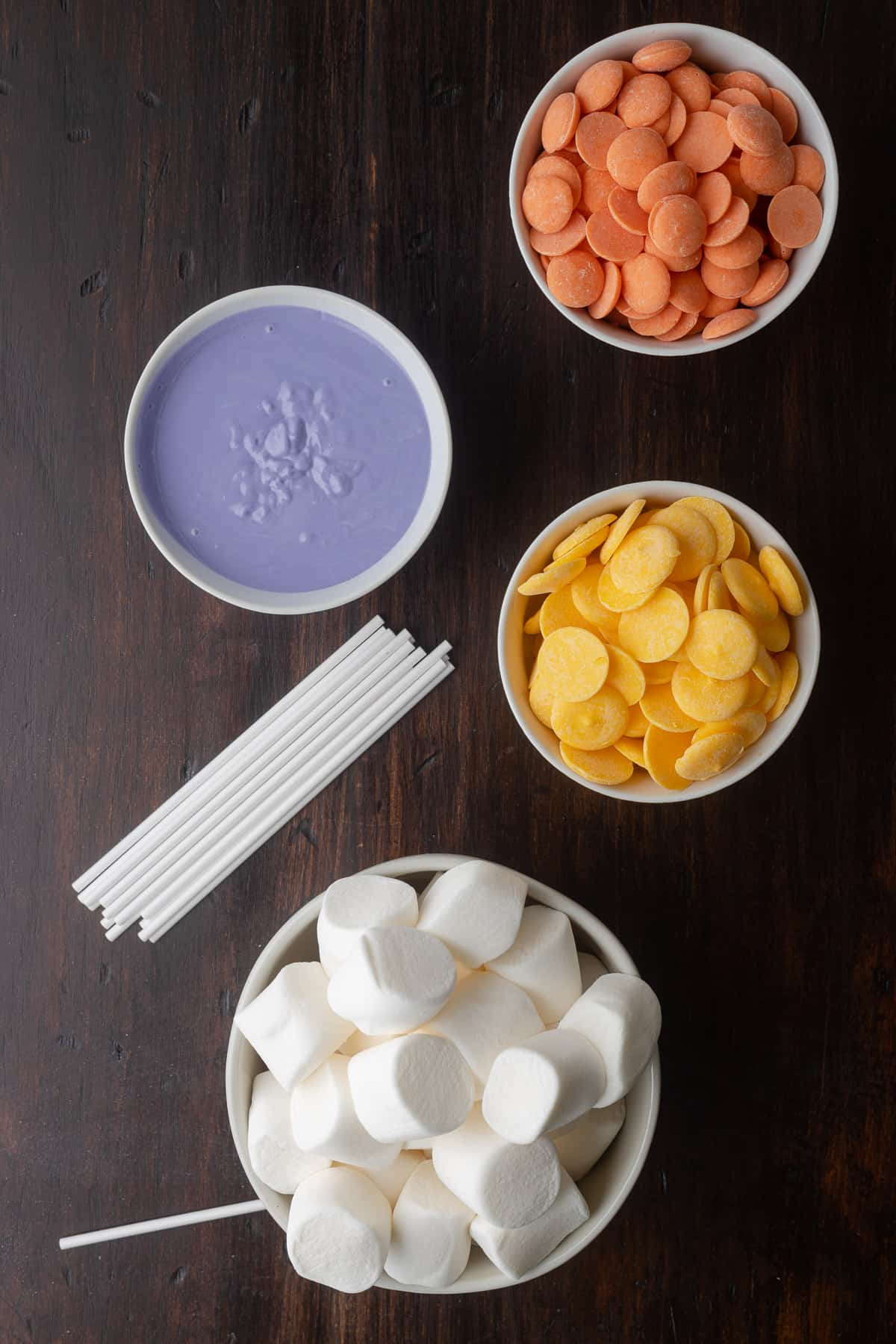 purple, orange, and yellow candy melts in bowls with treat sticks and large marshmallows nearby.