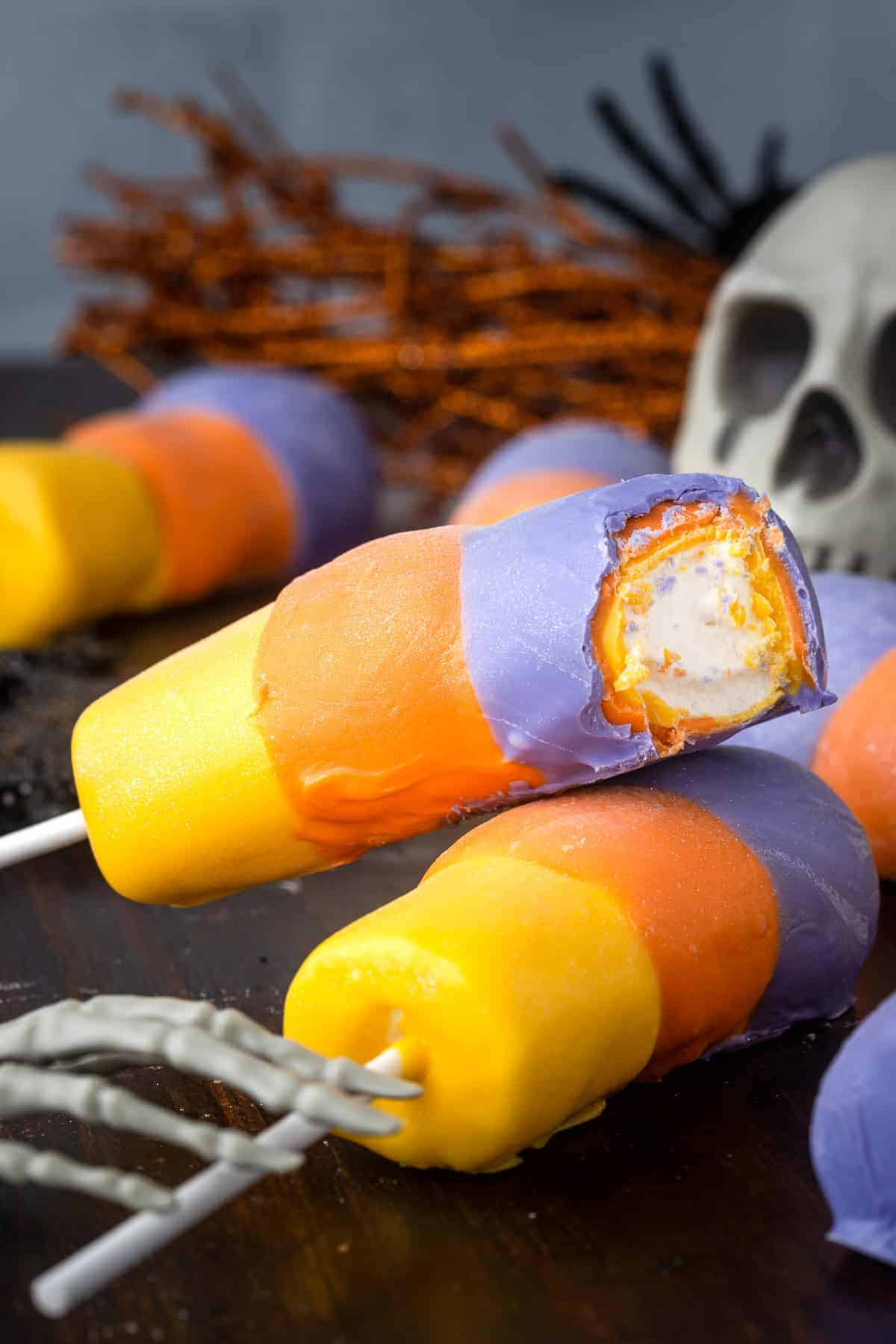 two hocus pocus themed chocolate covered marshmallow pops next to Halloween decorations.