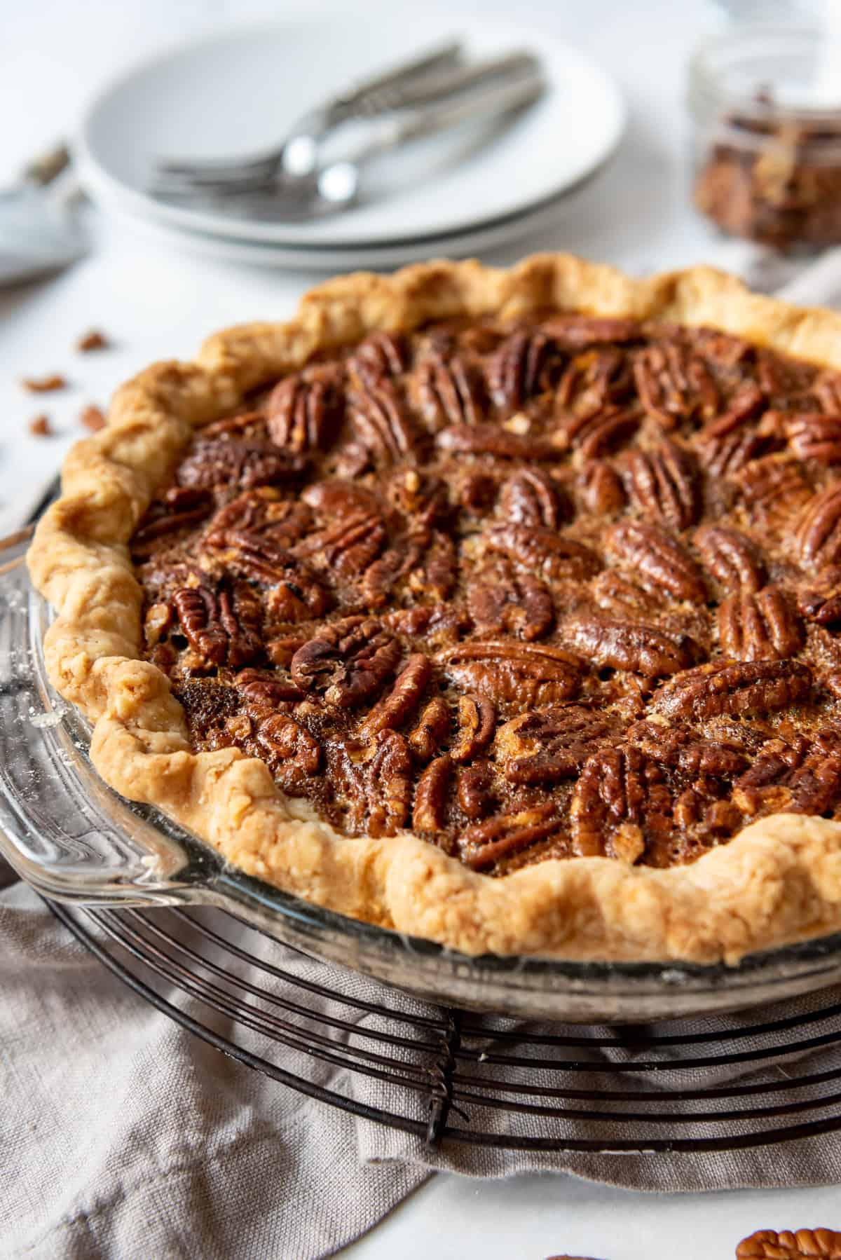 a classic American pecan pie in front of dessert plates with forks.