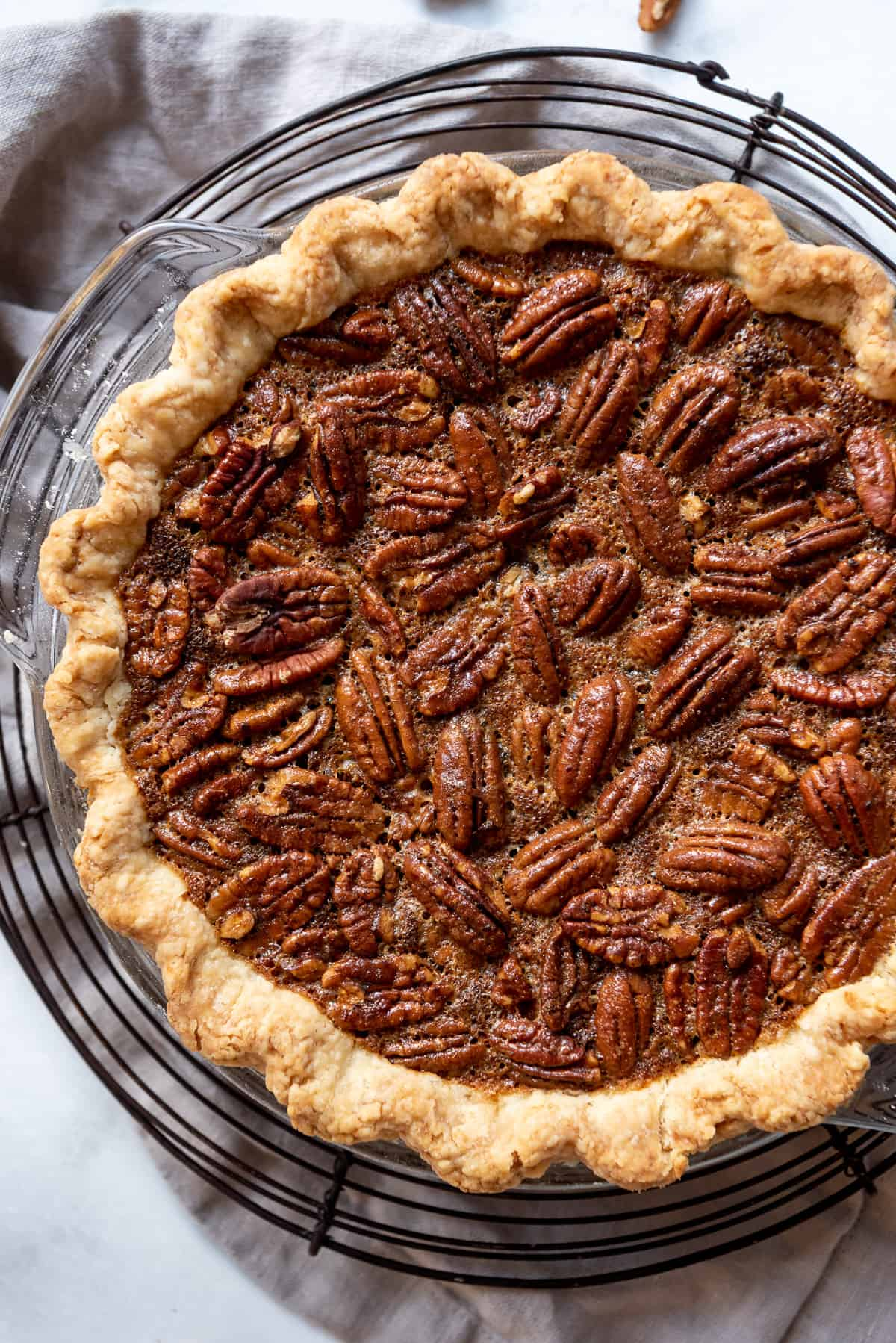 an overhead image of the caramelized top of a homemade pecan pie cooling on a black wire rack.