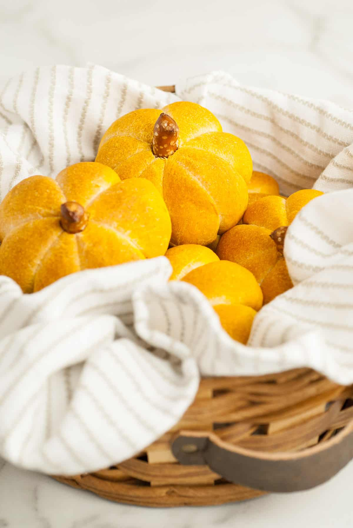 a basket lined with a linen napkin and filled with homemade pumpkin dinner rolls.