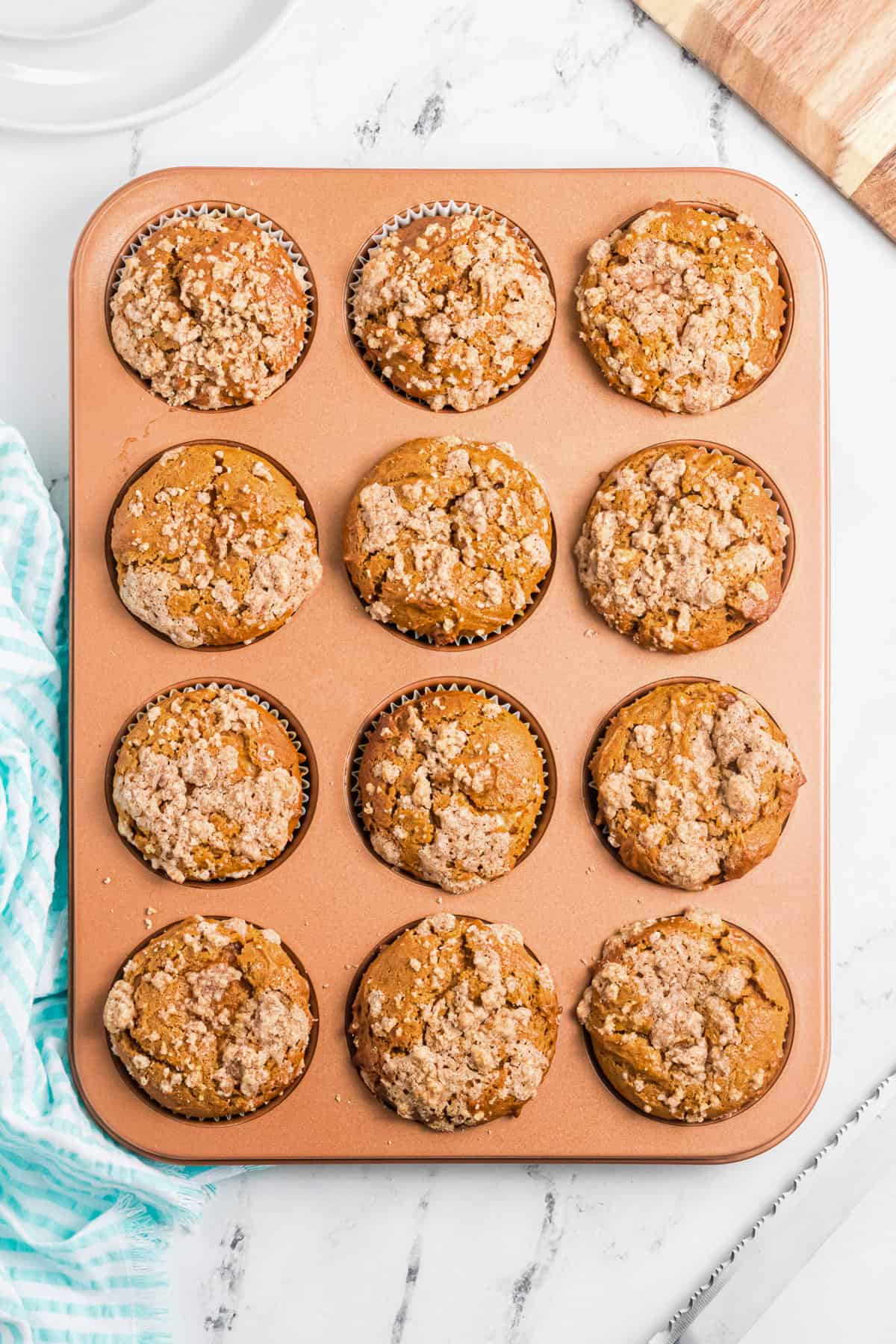 a muffin pan with 12 pumpkin cream cheese muffins topped with cinnamon streusel.