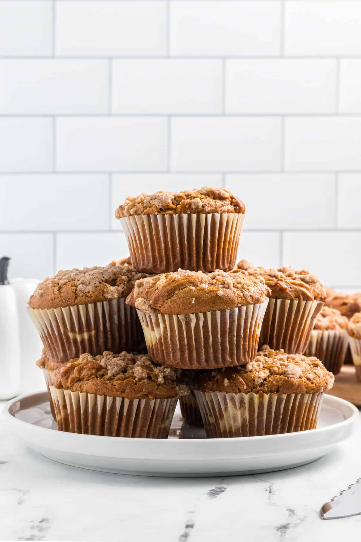 a plate piled with a stack of pumpkin cream cheese muffins.