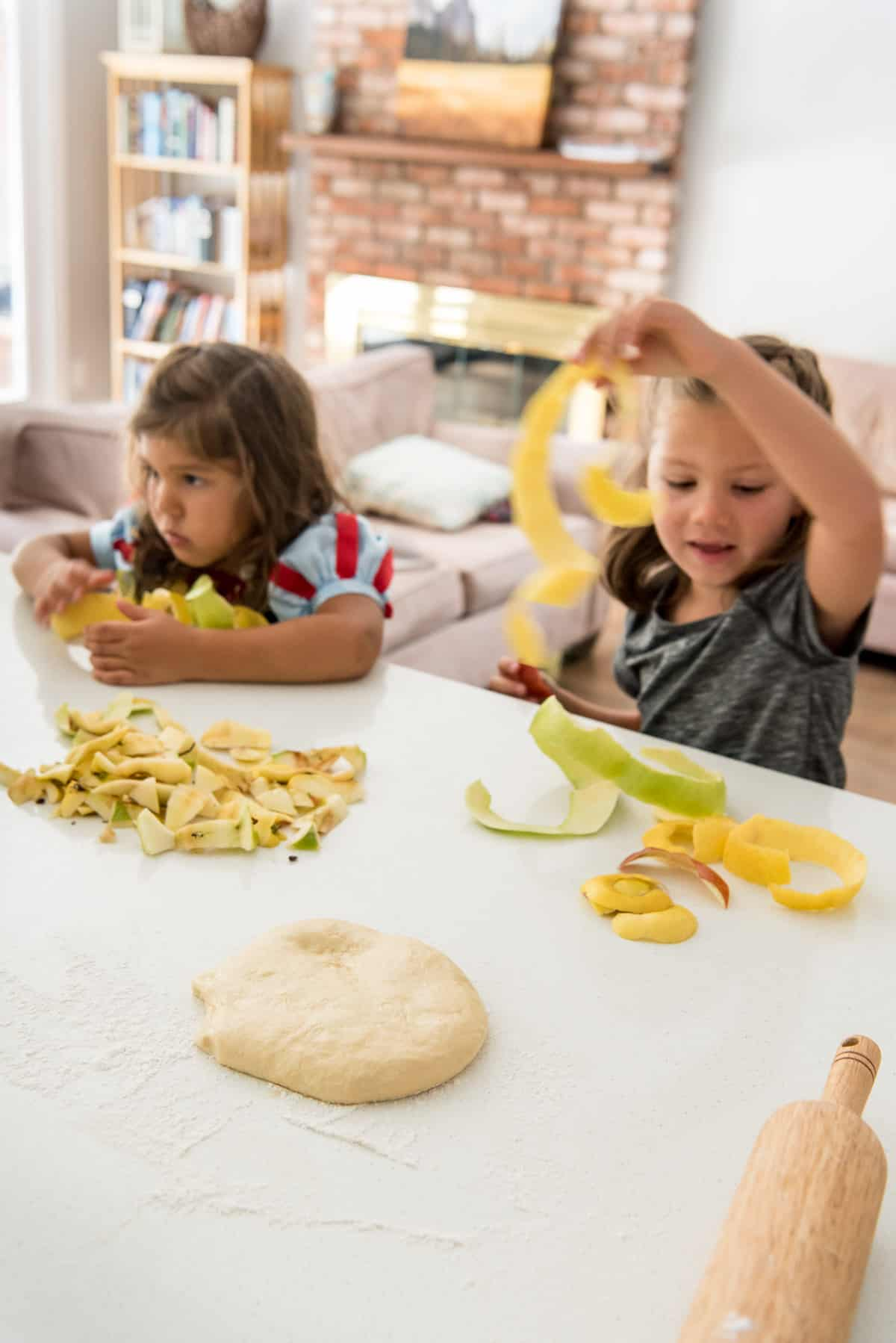 two young children at a counter with apple peels in front of homemade strudel dough and a rolling pin.