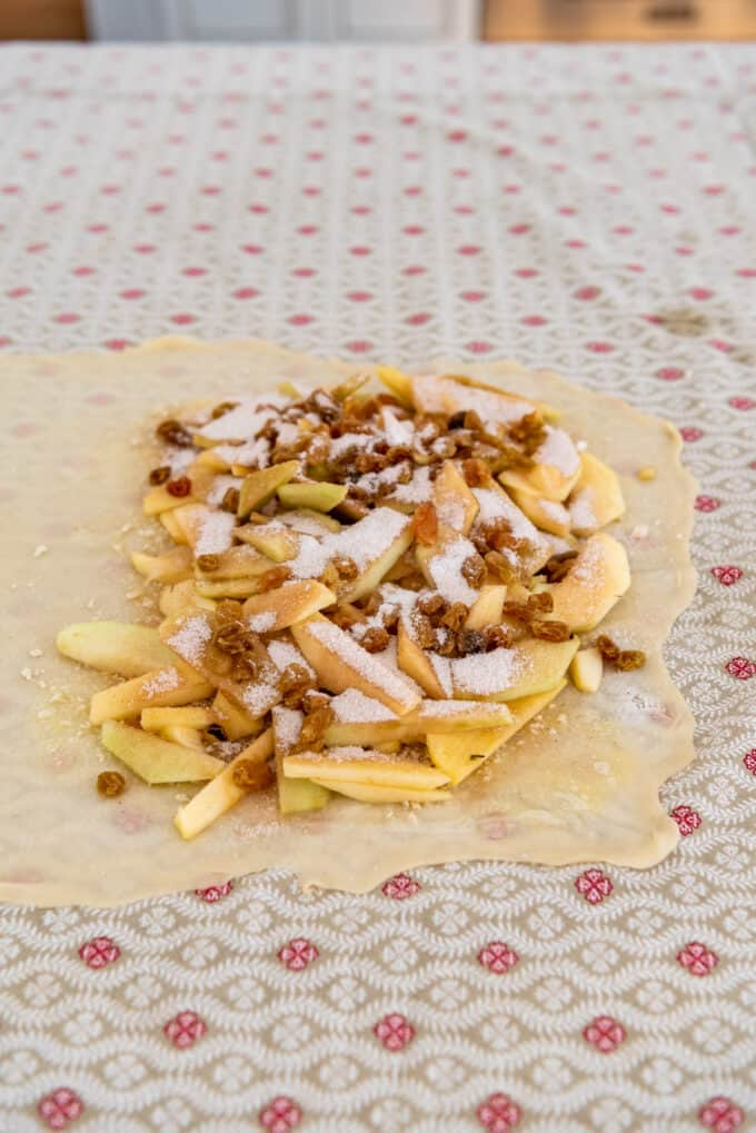 thinly sliced apples sprinkled with cinnamon, sugar, and raisins on a thin pastry dough.