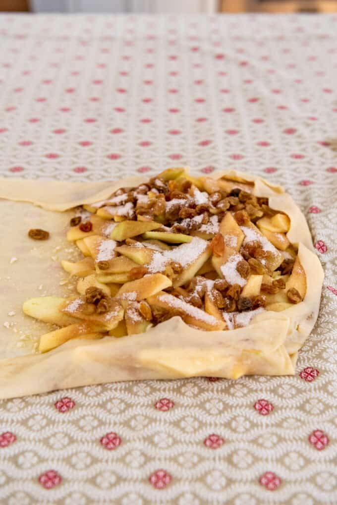 homemade strudel dough folded over an apple, cinnamon, sugar, and raisin filling.