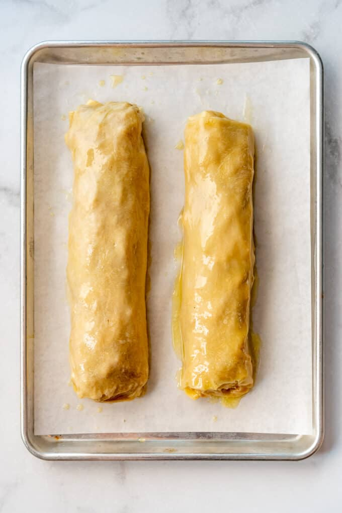 two apple strudel rolls brushed with melted butter on a baking sheet lined with parchment paper.