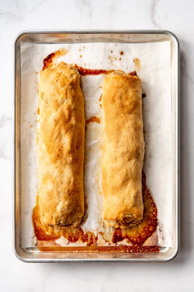 an overhead image of two long rolls of apple strudel before being sliced on a baking sheet lined with parchment paper.