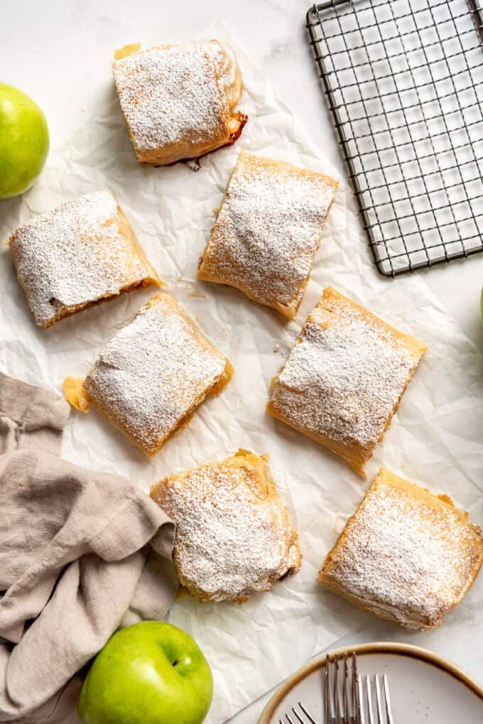 an overhead image of apfelstrudel slices next to a brown linen napkin and green apples.