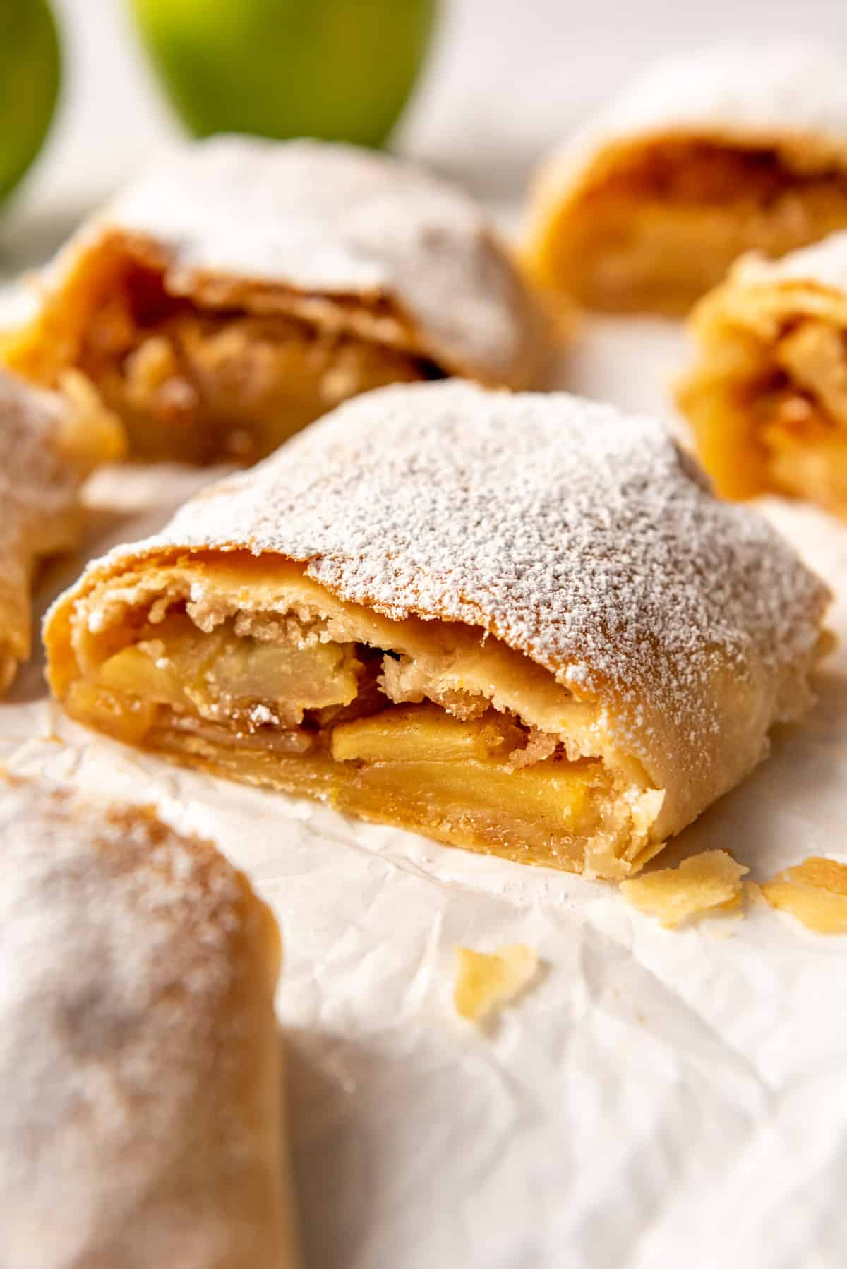 flaky homemade pastry dusted with powdered sugar around an apple filling on a piece of white parchment paper.