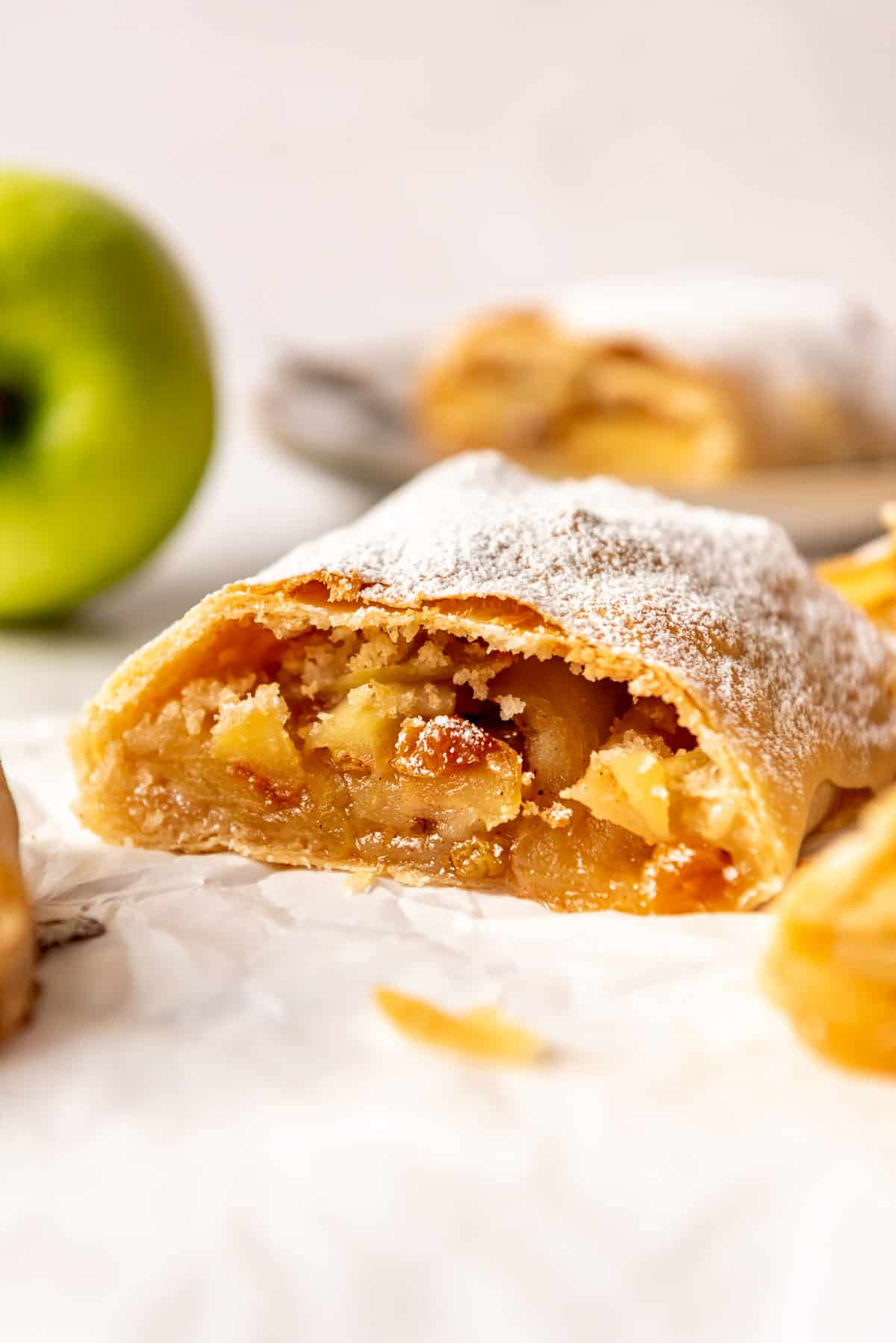 a slice of German apple strudel with raisins in front of a Granny Smith apple.