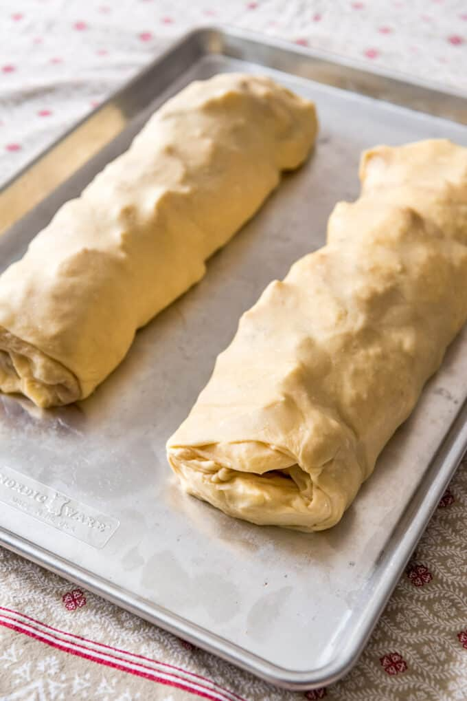 two rolls of apple strudel on a baking sheet before being baked.