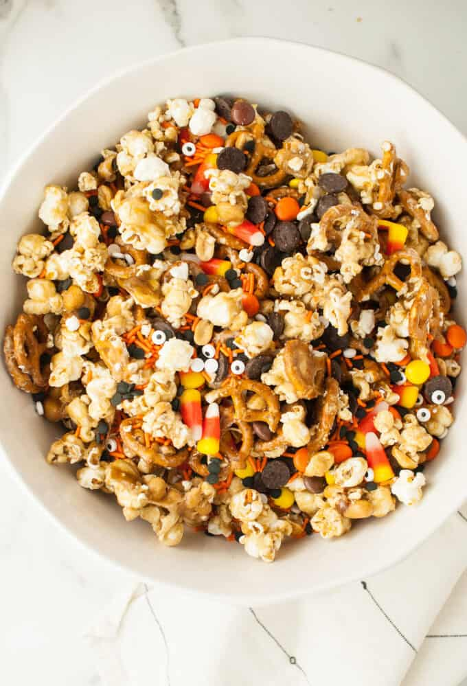 A large white bowl filled with caramel corn, candy corn, pretzels, chocolate, and peanuts.