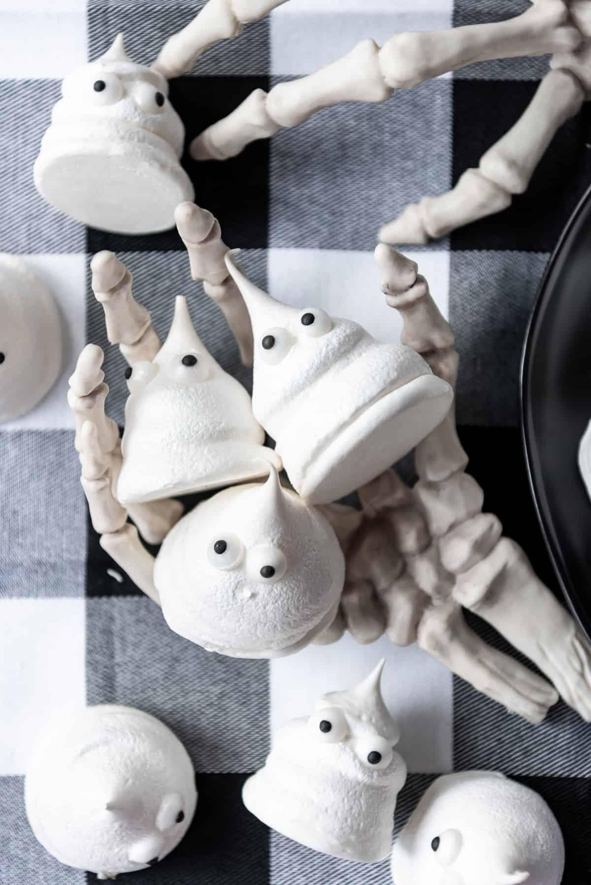 Three ghost meringues in a plastic skeleton hand.