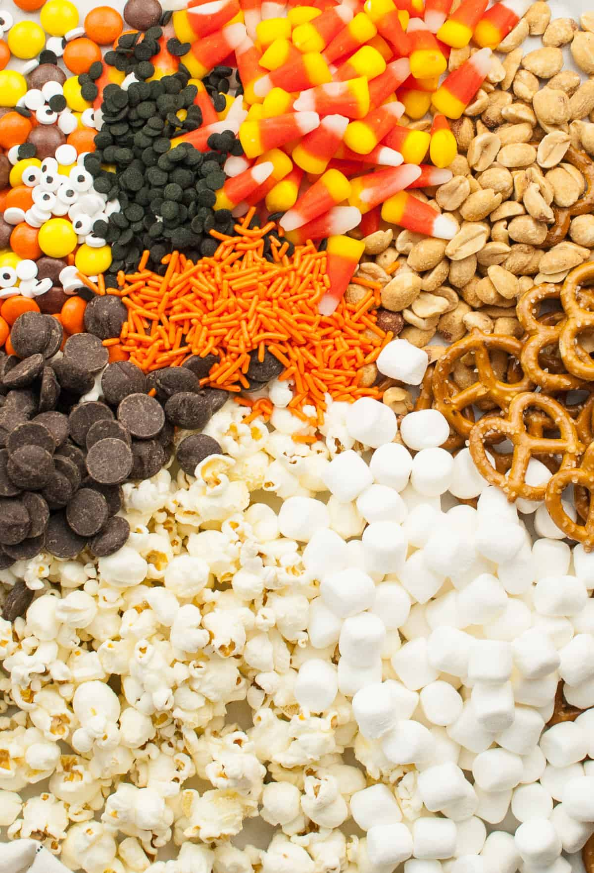 Clockwise from top: candy corn, peanuts, pretzels, marshmallows, popcorn, chocolate chips, and Halloween sprinkles.