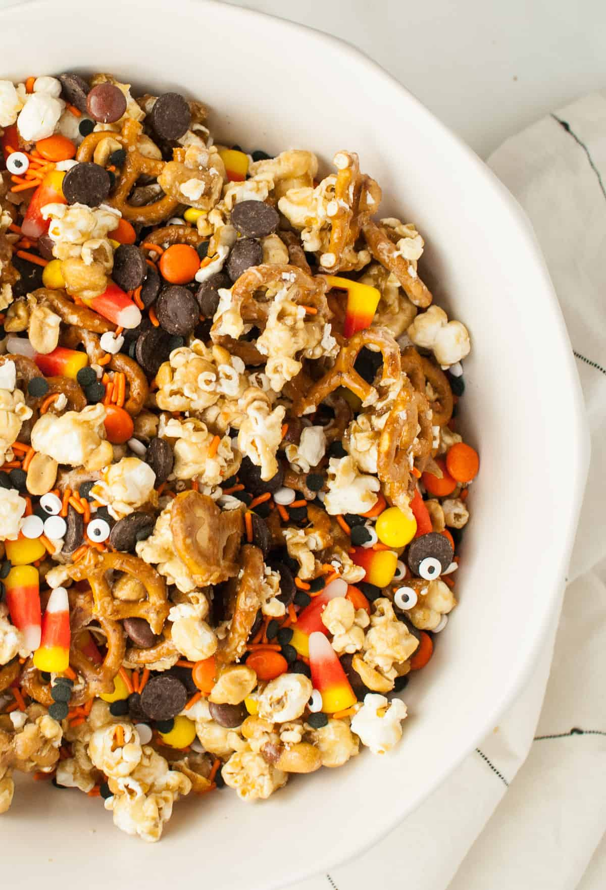 A large white bowl filled with Halloween snack mix.