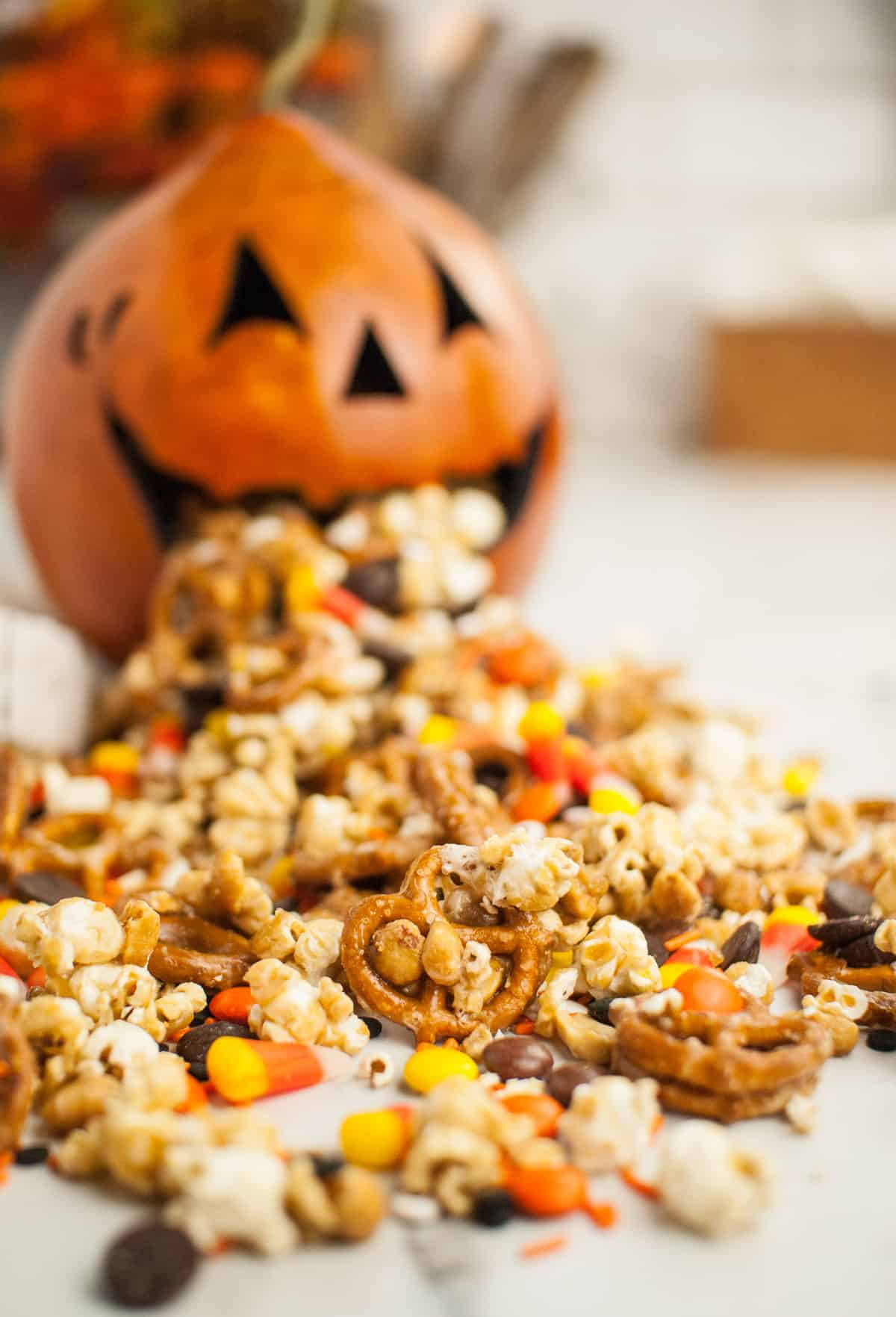 Halloween snack mix spilling from a jack-o-lantern's mouth.